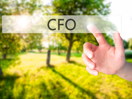 financial officer: CFO (Chief Financial Officer) - Hand pressing a button on blurred background concept . Business, technology, internet concept. Stock Photo