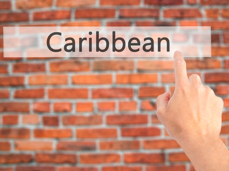 Caribbean - Hand pressing a button on blurred background concept . Business, technology, internet concept. Stock Photo