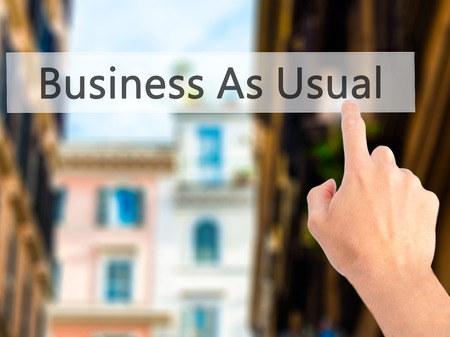 usual: Business As Usual - Hand pressing a button on blurred background concept . Business, technology, internet concept. Stock Photo