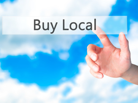Buy Local - Hand pressing a button on blurred background concept . Business, technology, internet concept. Stock Photo