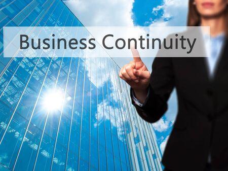 Business Continuity - Businesswoman pressing high tech  modern button on a virtual background. Business, technology, internet concept. Stock Photo Standard-Bild
