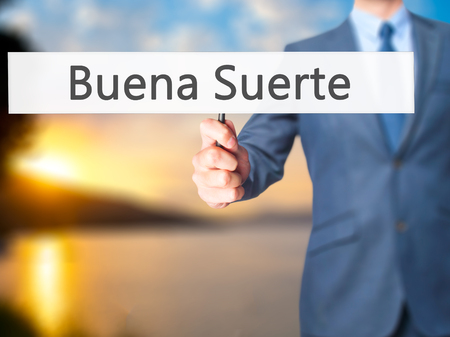 goodluck: Buena Suerte ( Good Luck in Spanish) - Business man showing sign. Business, technology, internet concept. Stock Photo Stock Photo