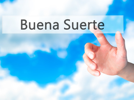 goodluck: Buena Suerte ( Good Luck in Spanish) - Hand pressing a button on blurred background concept . Business, technology, internet concept. Stock Photo