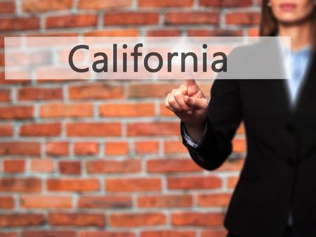 California - Businesswoman pressing high tech  modern button on a virtual background. Business, technology, internet concept. Stock Photo