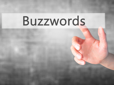 composing: Buzzwords - Hand pressing a button on blurred background concept . Business, technology, internet concept. Stock Photo