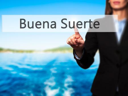 goodluck: Buena Suerte ( Good Luck in Spanish) - Businesswoman pressing high tech  modern button on a virtual background. Business, technology, internet concept. Stock Photo