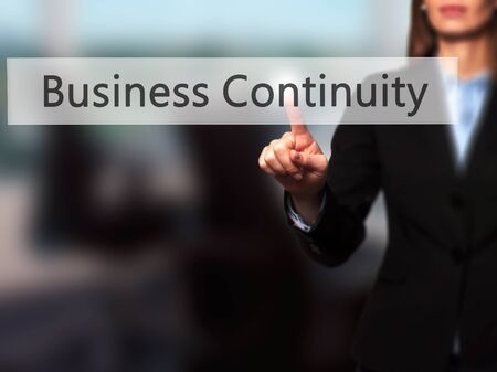 iscp: Business Continuity - Businesswoman pressing high tech  modern button on a virtual background. Business, technology, internet concept. Stock Photo Stock Photo