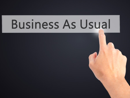 predictable: Business As Usual - Hand pressing a button on blurred background concept . Business, technology, internet concept. Stock Photo