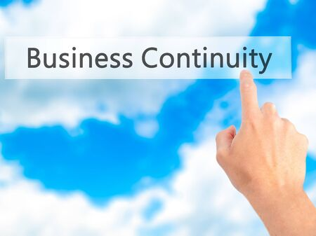 continuity: Business Continuity - Hand pressing a button on blurred background concept . Business, technology, internet concept. Stock Photo