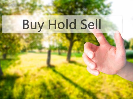 Buy Hold Sell - Hand pressing a button on blurred background concept . Business, technology, internet concept. Stock Photo