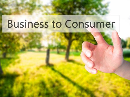 Business to Consumer - Hand pressing a button on blurred background concept . Business, technology, internet concept. Stock Photo