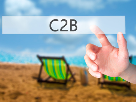reverse: C2B - Hand pressing a button on blurred background concept . Business, technology, internet concept. Stock Photo