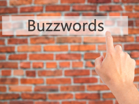 Buzzwords - Hand pressing a button on blurred background concept . Business, technology, internet concept. Stock Photo