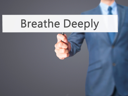 deeply: Breathe Deeply - Businessman hand holding sign. Business, technology, internet concept. Stock Photo
