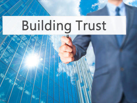 liable: Building Trust - Businessman hand holding sign. Business, technology, internet concept. Stock Photo
