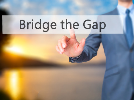 bridging the gaps: Bridge the Gap - Businessman hand touch  button on virtual  screen interface. Business, technology concept. Stock Photo