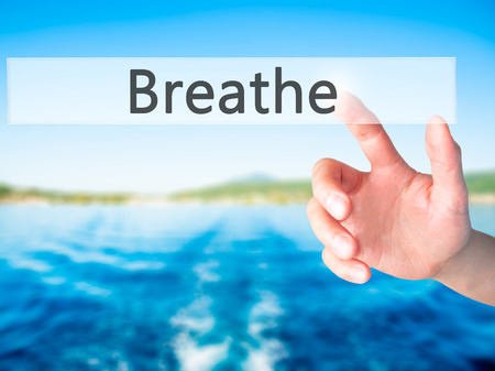 Breathe - Hand pressing a button on blurred background concept . Business, technology, internet concept. Stock Photo Stock Photo