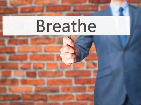 Breathe - hombre de negocios mano que sostiene la señal. Negocios, la tecnología, el concepto de internet. Foto de stock