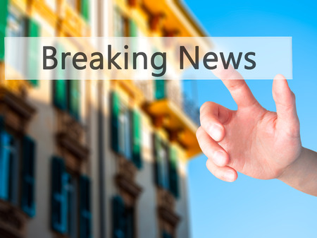 annoucement: Breaking News - Hand pressing a button on blurred background concept . Business, technology, internet concept. Stock Photo