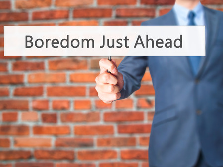 boredom: Boredom Just Ahead - Businessman hand holding sign. Business, technology, internet concept. Stock Photo