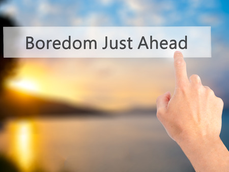 boredom: Boredom Just Ahead - Hand pressing a button on blurred background concept . Business, technology, internet concept. Stock Photo Stock Photo