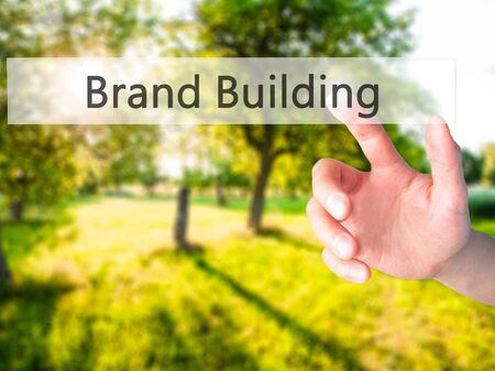 Brand Building - Hand pressing a button on blurred background concept . Business, technology, internet concept. Stock Photo Stock Photo