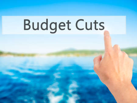 Budget Cuts - Hand pressing a button on blurred background concept . Business, technology, internet concept. Stock Photo