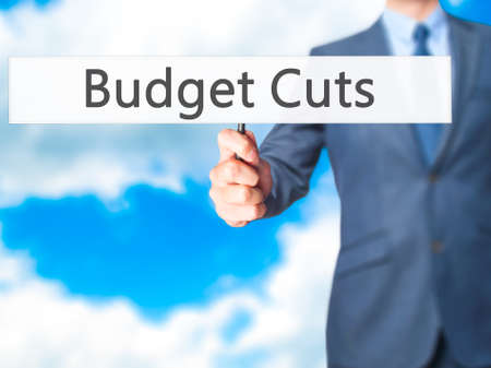 wasteful: Budget Cuts - Businessman hand holding sign. Business, technology, internet concept. Stock Photo