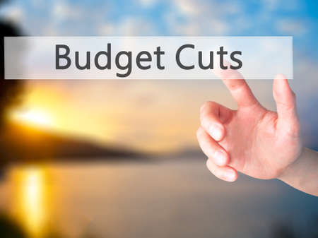 wasteful: Budget Cuts - Hand pressing a button on blurred background concept . Business, technology, internet concept. Stock Photo