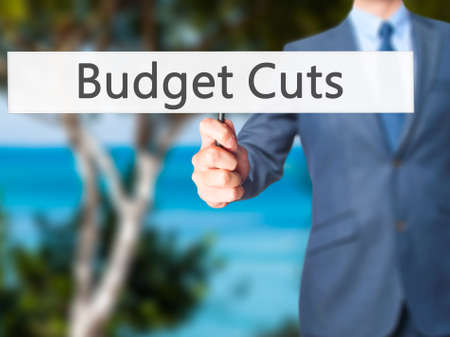 gov: Budget Cuts - Businessman hand holding sign. Business, technology, internet concept. Stock Photo