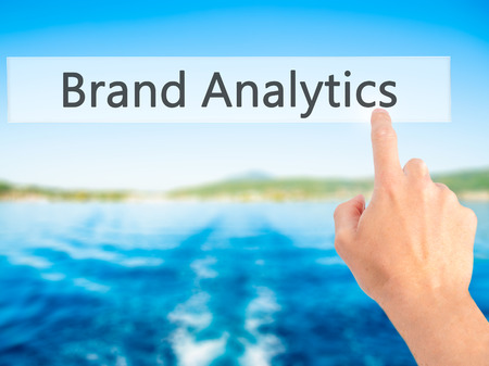 Brand Analytics - Hand pressing a button on blurred background concept . Business, technology, internet concept. Stock Photo Stock Photo