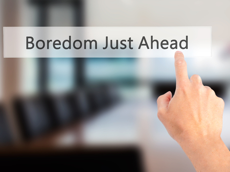 disinterested: Boredom Just Ahead - Hand pressing a button on blurred background concept . Business, technology, internet concept. Stock Photo Stock Photo