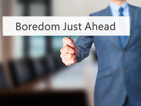 disinterested: Boredom Just Ahead - Businessman hand holding sign. Business, technology, internet concept. Stock Photo