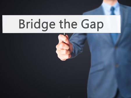 bridge the gap: Bridge the Gap - Businessman hand holding sign. Business, technology, internet concept. Stock Photo