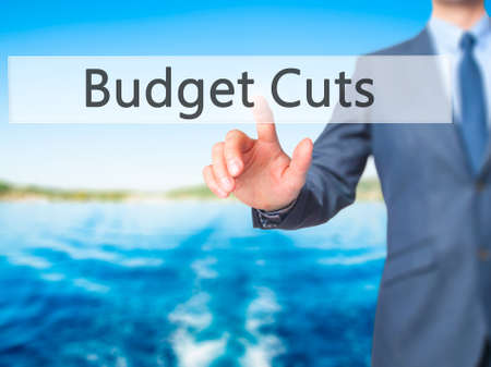 gov: Budget Cuts - Businessman hand touch  button on virtual  screen interface. Business, technology concept. Stock Photo Stock Photo