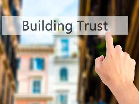 liable: Building Trust - Hand pressing a button on blurred background concept . Business, technology, internet concept. Stock Photo