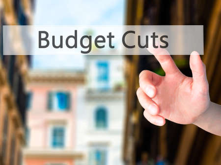 gov: Budget Cuts - Hand pressing a button on blurred background concept . Business, technology, internet concept. Stock Photo