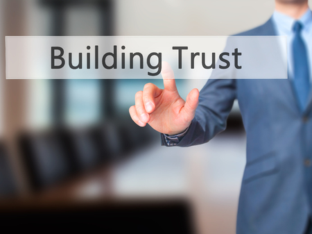 liable: Building Trust - Businessman hand touch  button on virtual  screen interface. Business, technology concept. Stock Photo