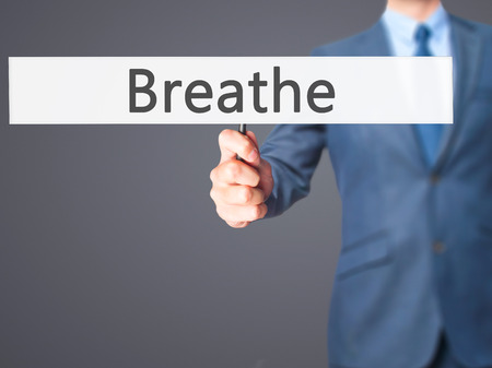 panicking: Breathe - Businessman hand holding sign. Business, technology, internet concept. Stock Photo