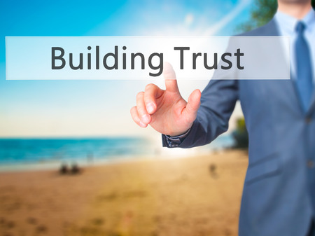building trust: Building Trust - Businessman hand touch  button on virtual  screen interface. Business, technology concept. Stock Photo