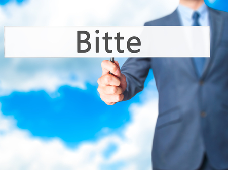 pleading: Bitte (Please in German) - Businessman hand holding sign. Business, technology, internet concept. Stock Photo