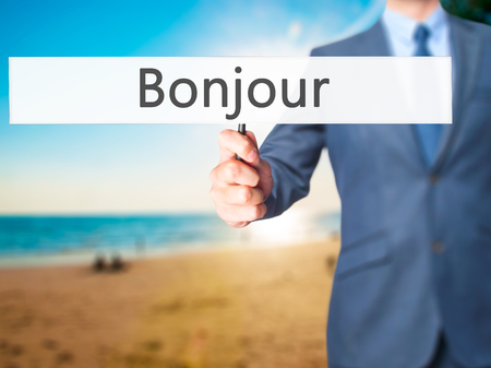 bonjour: Bonjour (Good Morning in French) - Businessman hand holding sign. Business, technology, internet concept. Stock Photo Stock Photo