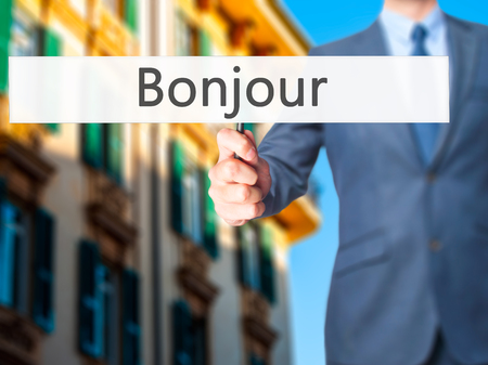 Bonjour (Good Morning in French) - Businessman hand holding sign. Business, technology, internet concept. Stock Photo Reklamní fotografie