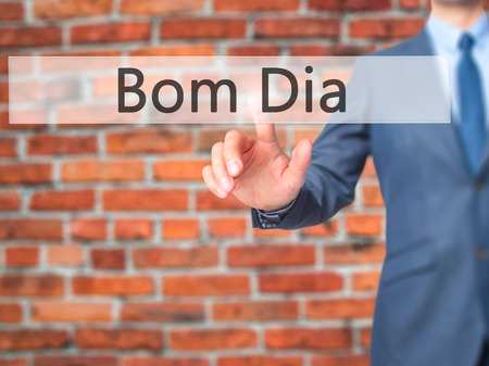 Bom Dia (In portuguese - Good Morning) - Businessman hand touch  button on virtual  screen interface. Business, technology concept. Stock Photo