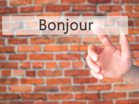 Bonjour (Good Morning in French) - Hand pressing a button on blurred background concept . Business, technology, internet concept. Stock Photo Stock Photo