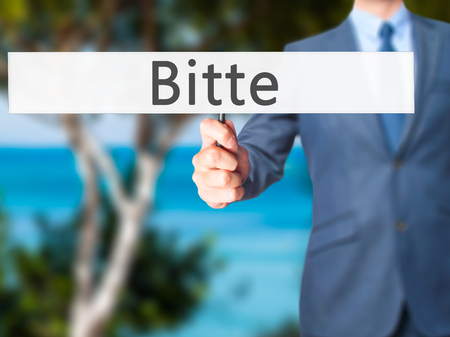 cordiality: Bitte (Please in German) - Businessman hand holding sign. Business, technology, internet concept. Stock Photo