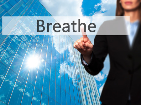 Breathe - Businesswoman pressing modern  buttons on a virtual screen. Concept of technology and  internet. Stock Photo