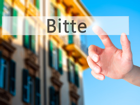 Bitte (Please in German) - Hand pressing a button on blurred background concept . Business, technology, internet concept. Stock Photo