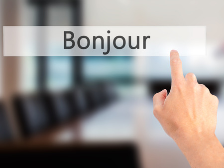 Bonjour (Good Morning in French) - Hand pressing a button on blurred background concept . Business, technology, internet concept. Stock Photo Reklamní fotografie