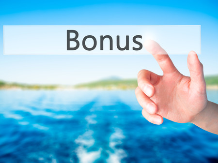 additional compensation: Bonus - Hand pressing a button on blurred background concept . Business, technology, internet concept. Stock Photo Stock Photo